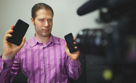 Man making video blog about mobile phones.
