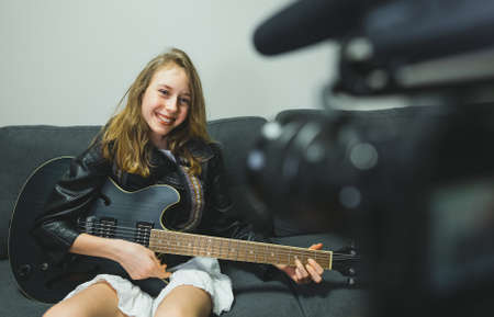 Teenage girl with semi-acoustic guitar in front of the video camera. Stockfoto