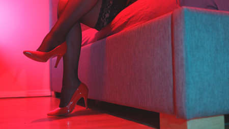 Sexual woman legs on the bed. Red-light district.