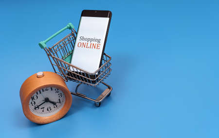 Shopping cart with smartphone and clock. Online shopping concept.