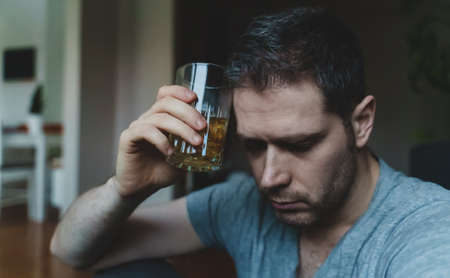 Exhausted drunk man with glass of whiskey. Alcoholism concept.
