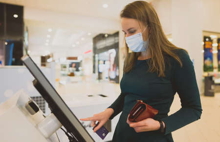 Woman using a self-service terminal in mall. Banque d'images