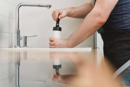 Plumber unclogging kitchen sink with professional force pump cleaner.