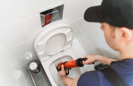 Plumber unclogging toilet with professional force pump cleaner.