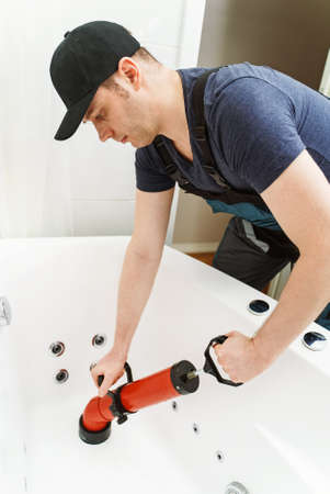 Plumber unclogging bathtub with professional force pump cleaner.