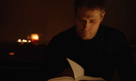 Handsome man reading book at night.