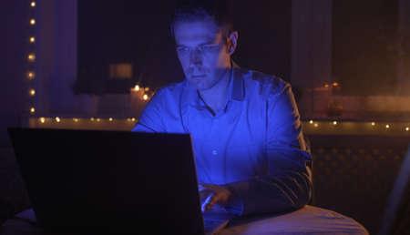 Man working on laptop pc at late night. Фото со стока