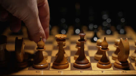 Person uses pawn on the board in chess game. Фото со стока