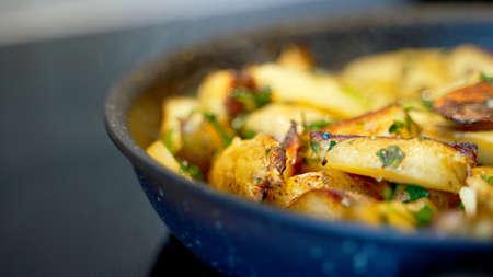 Fried village potatoes with herbs. Фото со стока