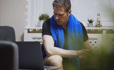 Man is watching an exercise on laptop. Sports activities at home.