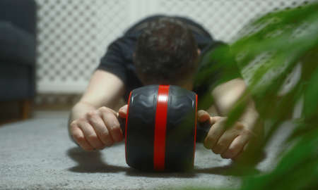 Man doing exercise with abs roller wheel at home.