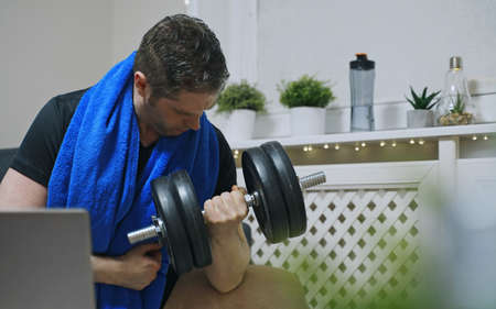 Man doing exercises with dumbbells at home.