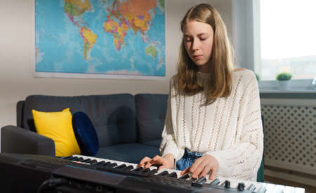 Teenage girl playing electronic musical instrument at home.