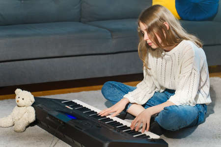 Teenage girl sitting on the floor and playing piano.