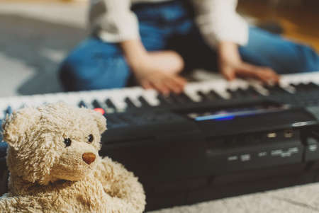 Girl sitting on the floor and playing piano. Close-up view.