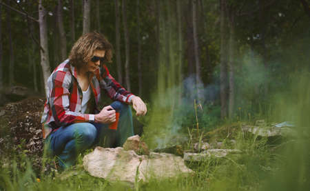 Man sits in front of bonfire in the forest.