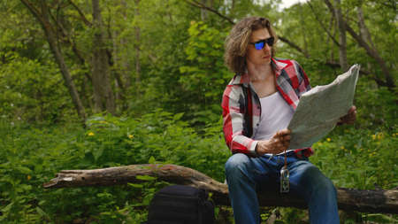 Man sits with compass and map. Orienteering.
