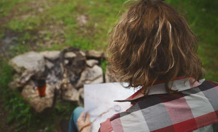 Man with map sits in front of bonfire in the forest.