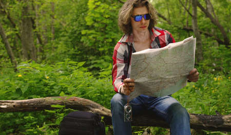 Male tourist with map in the forest. Фото со стока