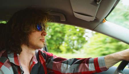 Man in blue sunglasses driving a car. Фото со стока