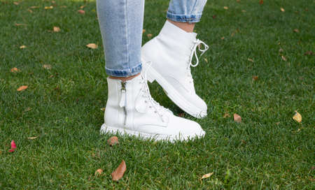 Woman legs in fashionable white casual boots on green grass background