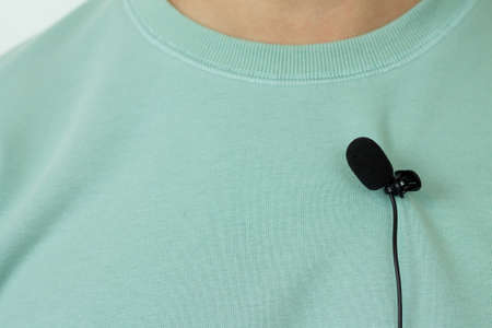 Small lavalier microphone or mic buttonhole on a man's t-shirt closeup Stock Photo
