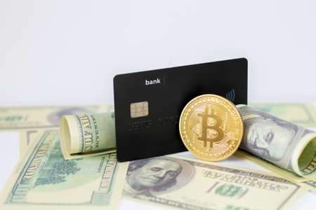 Credit card and bitcoin on dollar banknotes background with copy space
