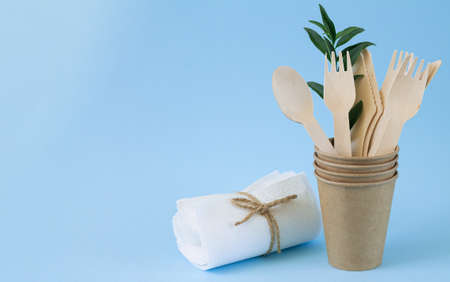 Eco natural wooden cutlery (knives, spoons, forks) in craft paper cup next to paper napkins on blue background. Eco sustainable living