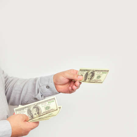 Businessman giving money us dollar bills close-up. Space for text Stockfoto