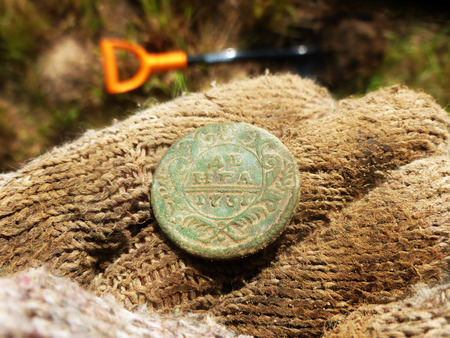 An ancient coin on the palm of your hand. Only from the ground. Stock Photo