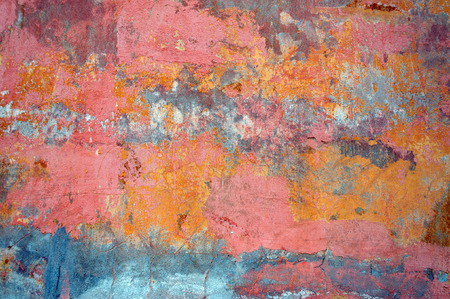 Bare concrete wall, peeling paint, pink and orange.