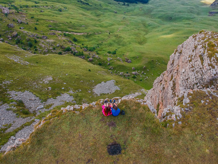 Couple in love sitting on a cliff of a mountain plateau, the view from the quadrocopter Imagens