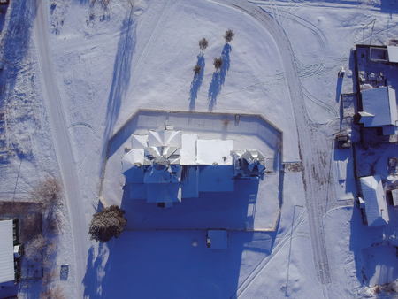 The temple in the Russian, winter, snowy village from the height of a quadrocopter on a clear sunny day