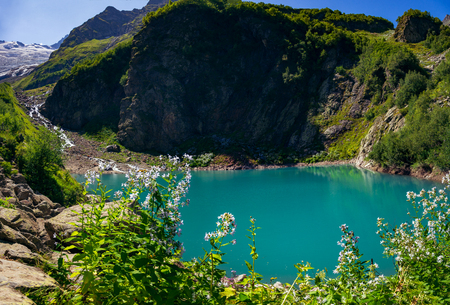 Alpine lake in the surroundings of Dombai. The Caucasus Mountains on a summer, clear day. Tourie Lake.