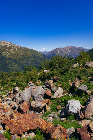 A large panorama of the path to the alpine lake through the huge stones. The Caucasus Mountains on a summer, clear day. Tourie Lake in the Outskirts of Dombai. . 写真素材