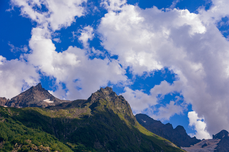 Massive peaks of the Caucasus Mountains in the snow in the surroundings of dombai in the clouds. Summer day.