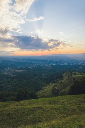 Puesta de sol sobre Kislovodsk desde una altura en verano, los rayos del sol a través de las nubes.