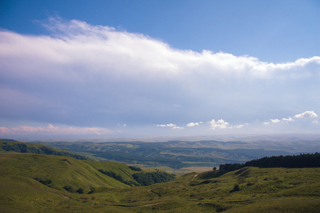 A huge panorama of the impending huge dark blue clouds over the mountains and hills in the summer