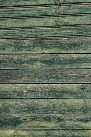 Macrotextuur van een houten hek met gebarsten groene verf. Stockfoto