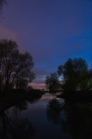 Large panorama of the most beautiful, scarlet sunset over the river in the spring
