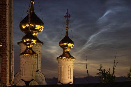 Cúpulas doradas de la iglesia sobre un fondo de nubes noctilucentes de cerca en una noche de verano. Foto de archivo