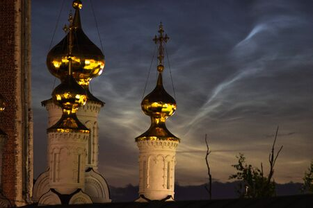 Golden domes of the church on a background of Noctilucent clouds close up on a summer night. Stock fotó