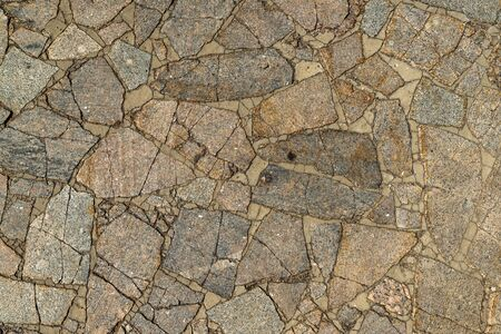 The texture of the sidewalk of chaotic granite stones of different colors with many cracks Standard-Bild