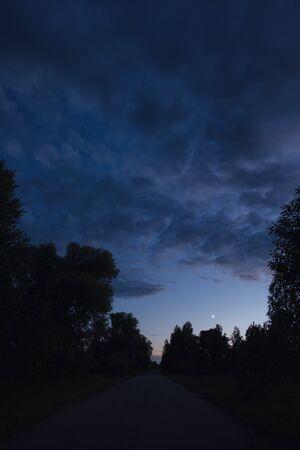 La strada nella sera d'estate, la luna tra le nuvole