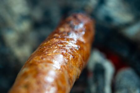 Sausage roasted on the coals in the fire, impaled on a stick. Junk food nature