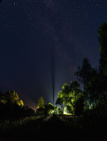 A ray of light going into the starry sky on a summer night.Lantern for the trees in the village