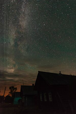 Starry sky with milky way over the houses in the Russian village summer night Banco de Imagens