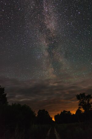 Road in the countryside summer starry night among the trees. Banco de Imagens