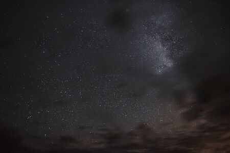 Milky way in the night sky through the clouds on a summer night Banco de Imagens - 129423436