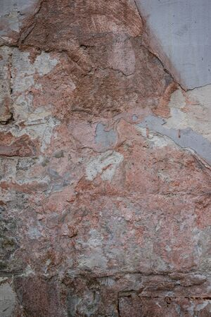 Macro texture of an old red brick wall and even separation of fallen plaster